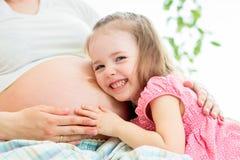 De buik van de luister zwangere moeder van het kindmeisje stock foto
