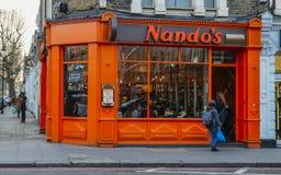De buitenkant van de vlam van Nando ` s roosterde PeriPeri-kippenrestaurant in Graaf` s Hof, Londen, het UK De ketting is Afro-Po stock afbeelding