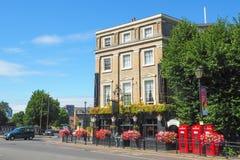 De buitenmening van het Mitre Hotel in Greenwich, Londen op een de zomerdag met de rode telefooncellen en de mensen die overgaan  Stock Foto