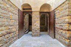 De buitenpassage van de baksteensteen met twee aangrenzende gewelfde geopende houten grungedeuren stock fotografie