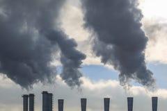 De buizen geven de donkere rook tegen een achtergrond van witte wolken en een blauwe hemel vrij Stock Foto