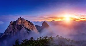De Bukhansanbergen wordt behandeld door ochtendmist en zonsopgang stock afbeelding