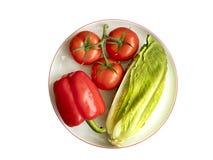 De Bulgaarse peper, de tak van tomaat en de snijsla liggen close-up op een witte ronde porseleinplaat met een granaatappelrand Stock Afbeeldingen