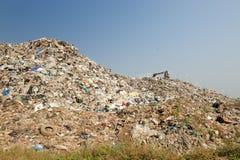 De bulldozer begraaft voedsel en industriële afvallen Stock Foto
