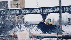 De bulldozer bestrooit een stapel van steenkool op het grondgebied van de elektrische centrale Steenkool met sneeuw wordt behande stock videobeelden