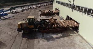 De bulldozer maakt het programma opent de transportband van een houtbewerkingsfabriek leeg Gele bulldozer dragende logboeken stock video