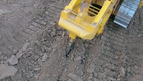 De bulldozer met schulpzaagsteel doordringt en maakt de grond op bouwwerf los stock videobeelden
