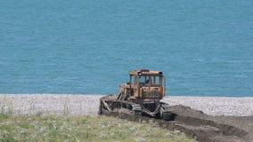 De bulldozer versterkt de kustlijn tegen de achtergrond van een kalme blauwe overzees Zonnige dag, de zomer stock videobeelden