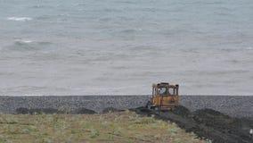 De bulldozer werkt om de oever tegen de achtergrond van het stormachtige overzees te versterken Hoofdzakelijk bewolkt stock video