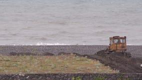 De bulldozer werkt om de oever tegen de achtergrond van het stormachtige overzees te versterken Hoofdzakelijk bewolkt stock footage