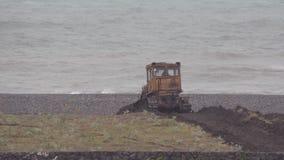 De bulldozer werkt om de oever tegen de achtergrond van het stormachtige overzees te versterken Hoofdzakelijk bewolkt Regen stock footage