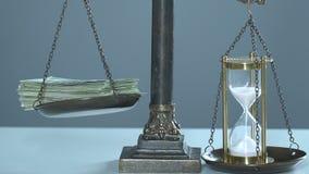 De bundel van geld en sandglasses op schalen, tijd is kostbaar, taxeert van het leven stock videobeelden