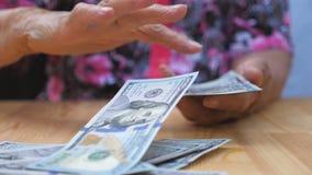 De bundel van de grootmoederholding van geld in handen en verspreidende vreemde valuta op het bureau Wapens van oude vrouw die we stock videobeelden