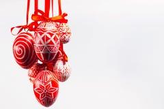 De bundel van paaseieren met volks Oekraïens patroon hangt op rode linten van linkerkant op witte achtergrond Oekraïense traditio Stock Afbeeldingen