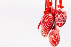De bundel van paaseieren met volks Oekraïens patroon hangt op rode linten van rechterkant op witte achtergrond Oekraïens traditio Stock Afbeelding