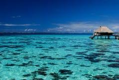 De bungalow van Overwater op een blauwe lagune stock foto