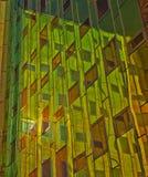 De bureaubouw met groene gele bezinningen in vensters Stock Afbeeldingen