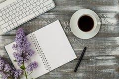 De bureaulijst met computer, levering, kop van koffie en pioen bloeit Witte Houten Achtergrond Koffiepauze, ideeën, nota's, g royalty-vrije stock foto's