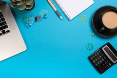 De bureaulijst met reeks kleurrijke levering, wit leeg notastootkussen, kop, pen, PC, verfrommelde document, bloem op blauwe acht royalty-vrije stock afbeelding