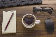 De bureaulijst met zaken heeft, koffie, blocnote, notitieboekje, c bezwaar Stock Foto's