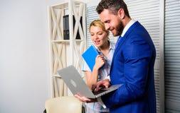 De bureaupartner toont online de statistieken van informatiegegevens Werkgever en secretaresse of het hulpwerk als team vraag stock fotografie