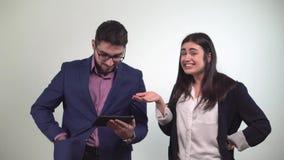 De bureausituatie tussen partners een mens bekijkt de tablet en het meisje nadat de dans autosleutel binnen gewonnen krijgt stock footage