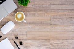 De bureauvlakte legt mening met laptop, muis, boom, zwarte klem, de kop van de hart latte koffie, notitieboekje, potlood op houte stock fotografie