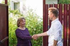 De buren bespreken het nieuws, die zich bij de omheining bevinden Een bejaarde die met een jonge mens spreken stock afbeelding