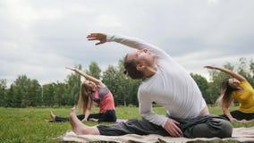 De bus onderwijst yoga voor vrouw - flexibiliteit opleiding in het park stock video