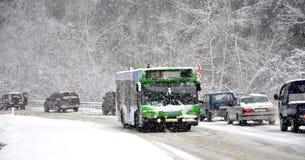 De bus van de pendel op de weg in de sneeuw Stock Afbeeldingen