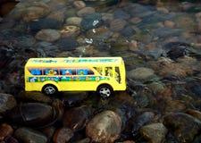 De bus van de school in water Stock Foto