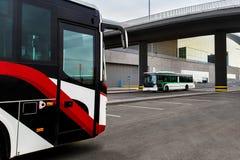 De bussen bevinden zich bij een bushalte stock fotografie
