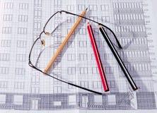De byggnadsplanet, exponeringsglasen och blyertspennan Royaltyfria Bilder