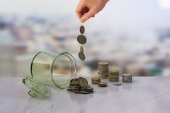 De cabeça para baixo o frasco das moedas e do fundo da mão, Imagens de Stock Royalty Free