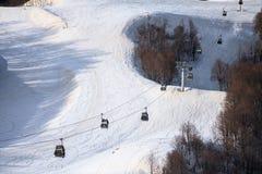 De cabines van de kabelbaanlift op sneeuw van de achtergrond skihelling mooi de winterlandschap Stock Fotografie