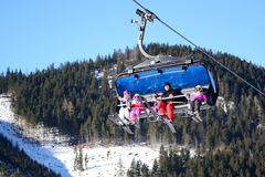 De cabines van Gelukkige kabelbaan met familie van skiërs in Jasna Low Tatras Stock Foto's
