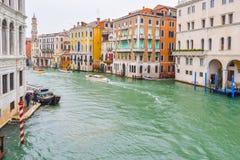 De cabines van de watertaxis/taxi en andere boten die op water tussen kleurrijke gotische Venetiaanse gebouwen op een regenachtig stock afbeeldingen