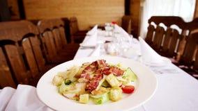 De Caesarsalade wordt gediend op een lijst, brengt de kelner een schotel met salade in het restaurant zet plaat op behandeld met  stock video