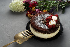 De cake die met chocolade wordt behandeld verfraaide frambozen, met een boeket van bloemen op een grijze achtergrond Royalty-vrije Stock Fotografie