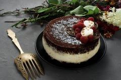 De cake die met chocolade wordt behandeld verfraaide frambozen, met een boeket van bloemen op een grijze achtergrond Royalty-vrije Stock Afbeeldingen