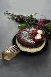De cake die met chocolade wordt behandeld verfraaide frambozen, met een boeket van bloemen op een grijze achtergrond Royalty-vrije Stock Foto's