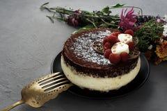 De cake die met chocolade wordt behandeld verfraaide frambozen, met een boeket van bloemen op een grijze achtergrond Royalty-vrije Stock Afbeelding