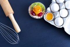 De cake, eieren in een dienblad met een deegrol en zwaait op de lijst royalty-vrije stock foto