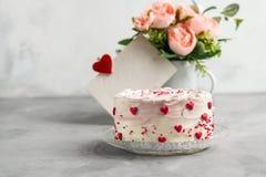 De cake met kleine harten en kleurrijk bestrooit op een plaat met koffie Grijze steenachtergrond Het drinken Stro in Glas Valenti stock foto