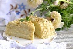 De cake is napoleon in een besnoeiing tegen de achtergrond van uitstekende textiel Een boeket van witte bloemen zoet ontbijt voor stock foto's
