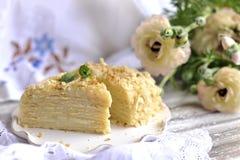 De cake is napoleon in een besnoeiing tegen de achtergrond van uitstekende textiel Een boeket van witte bloemen zoet ontbijt voor stock afbeeldingen