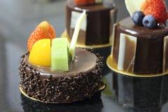 De cake van de chocolade die op zwarte achtergrond is ontsproten Stock Fotografie