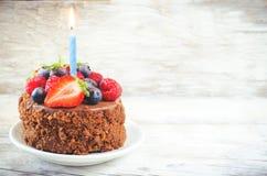 De cake van de chocoladeverjaardag met kaars, frambozen, bosbessen Stock Foto's