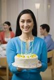 De cake van de de holdingsverjaardag van de vrouw met kaarsen Royalty-vrije Stock Afbeelding