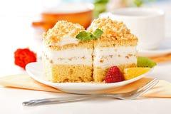 De cake van de slagroom met fruitstukken dat wordt versierd royalty-vrije stock afbeelding
